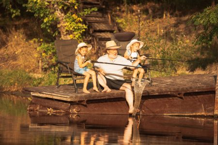 Cute little girls and their granddad are on fishing at the lake or river. Resting on pier near by water and forest in sunset time of summer day. Concept of family, recreation, childhood, nature.